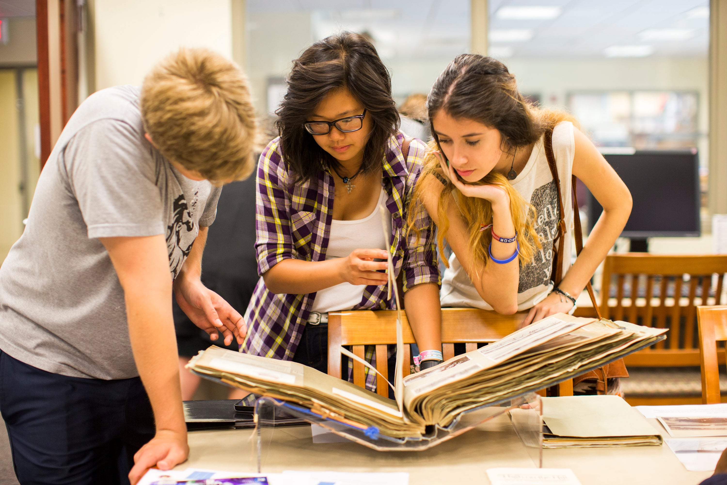 Color photo of three students viewing a scrapbook in the DCA Reading Room.