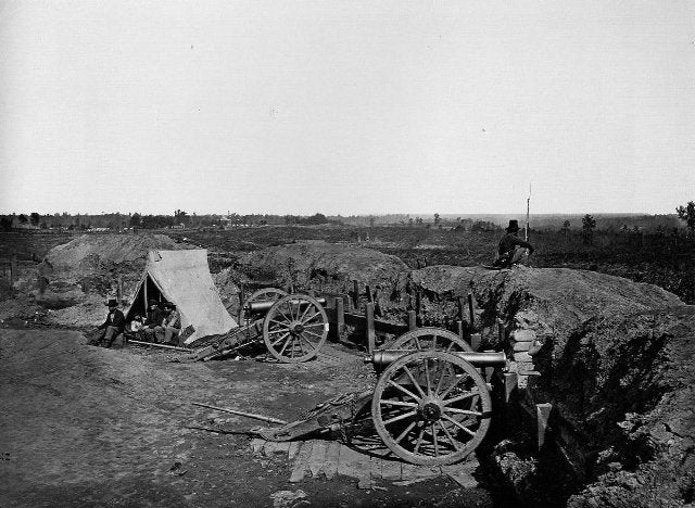 Civil War photo - Union soldiers in canvas tent while a comrade guards a captured Confederate bastion in the defense of Atlanta.