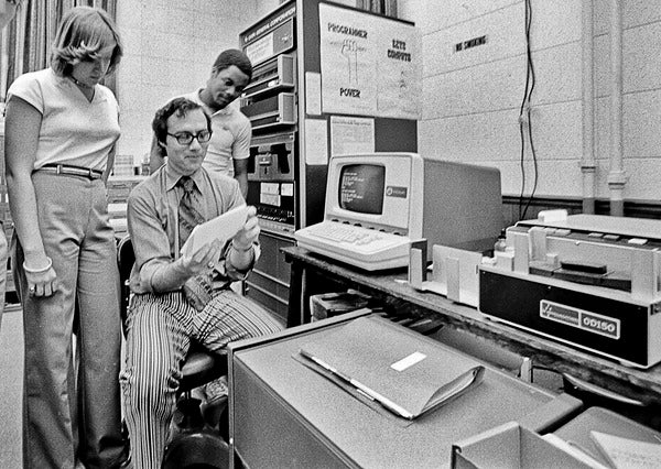 Black and white photo of a computer lab with three individuals at work.
