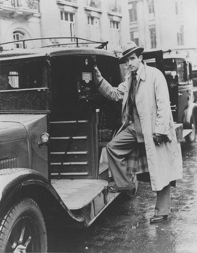 Black and white photograph of Edward R. Murrow standing next to a taxi cab.
