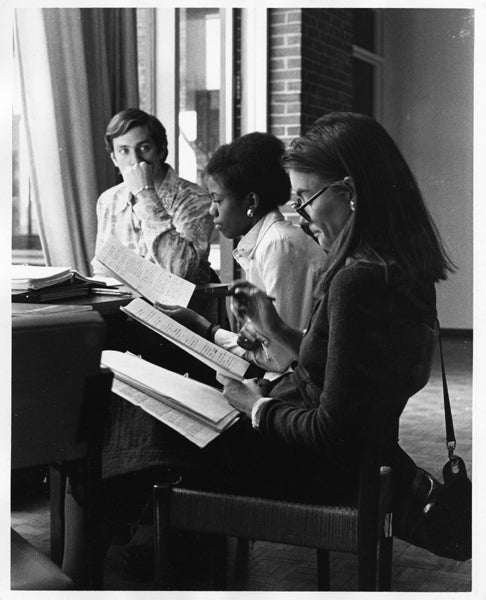 Black and white photograph of three Fletcher School students studying in the library.